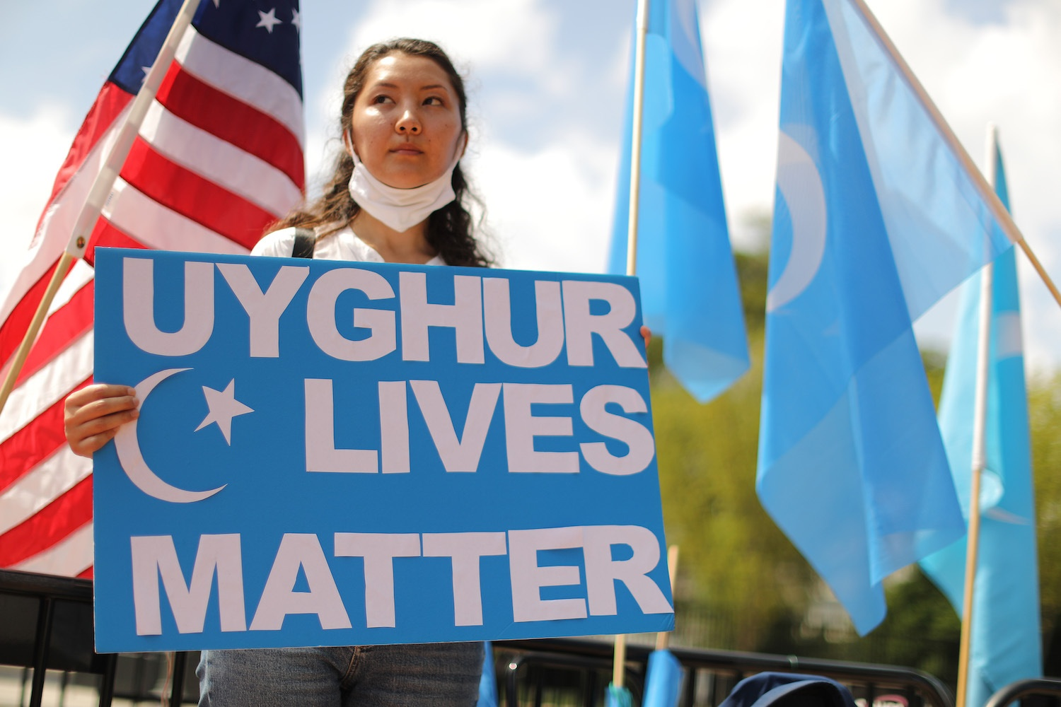 A protester holding a placard supporting the Uyghurs